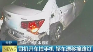 司机开车捡手机 轿车漂移撞路灯图片
